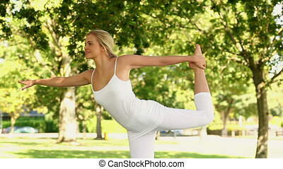 Pretty blonde woman doing yoga in the park on a sunny day
