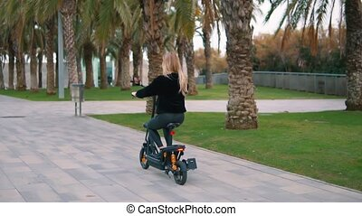 Pretty blonde woman driving electric bike in city park -...