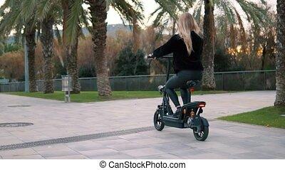 Pretty blonde woman driving electric bike in city park