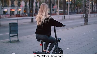 Pretty blonde woman driving electric bike in the city -...