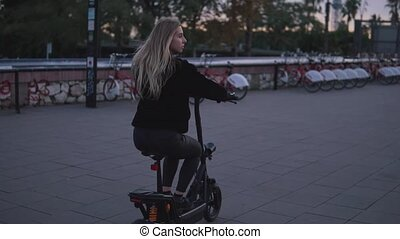 Pretty blonde woman driving electric bike in the city