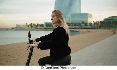 Pretty blonde woman driving electric bike near sea. Modern...