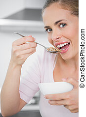 Pretty blonde woman eating bowl of cereal