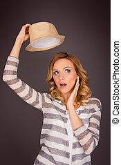 Pretty blonde woman holding hat under her head