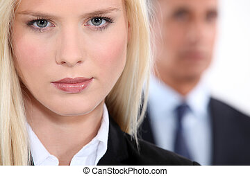 Pretty blonde woman in a suit with an older man out of focus in the background