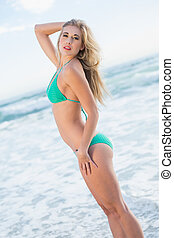 Pretty blonde woman in green bikini posing looking at camera