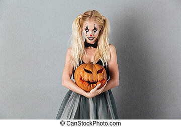 Pretty blonde woman in halloween clown make-up