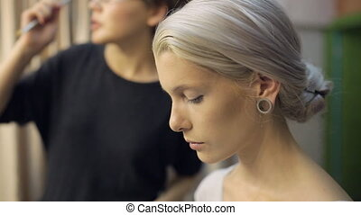 Pretty blonde woman prepares for photo shoot in dressing room.