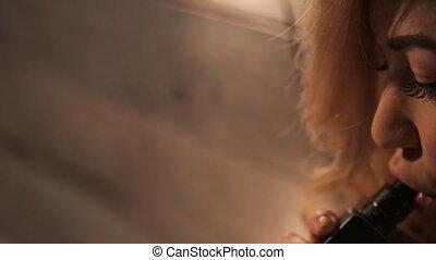 Pretty blonde woman smokes electronic generator of vapor