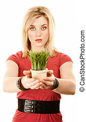 Pretty blonde woman with grass in small pot