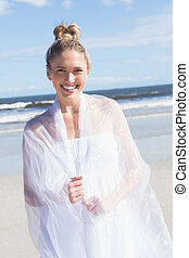 Pretty blonde wrapped in white shawl on the beach