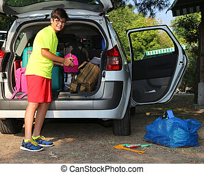 boy with glasses loaded the luggage in the trunk of the car