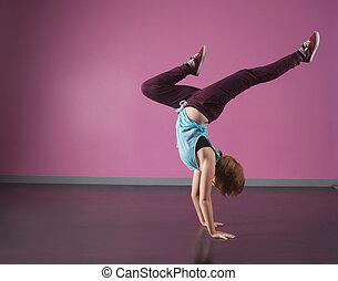 Pretty break dancer doing a handstand in the dance studio