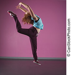 Pretty break dancer leaping mid air in the dance studio
