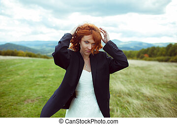 Pretty bride adjusts her hair posing in groom's jacket on the field in windy weather