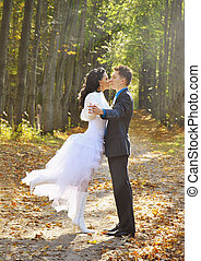 Bride and groom walking in autumn pine forest
