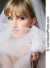 Close-up portrait of young beautiful thoughtful bride in bridal veil