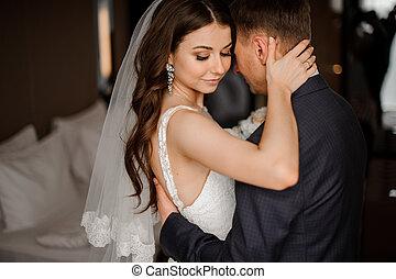 pretty bride hugs a elegance bridegroom - pretty brunette...