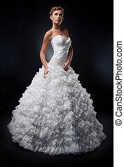 Pretty bride in white nuptial dress posing in studio