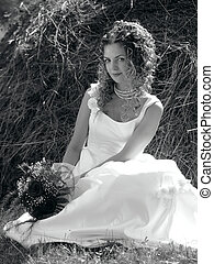 Pretty bride sat in field