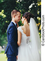 Pretty bride touches groom's neck stnading under a green tree