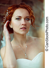 Pretty bride with blue eyes touches her red hair delicately