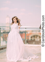 Pretty bride with long curly hair in wedding dress posing on the terrace