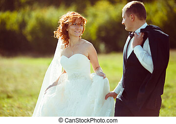 Pretty bride with red hair looks at a groom standing on the field