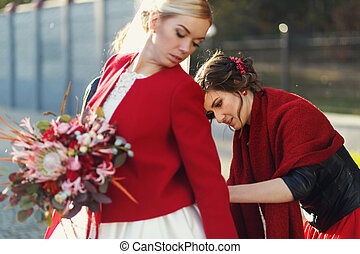 Pretty bridesmaid in red adjusts a corset on a beautiful blonde bride