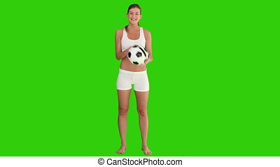Pretty brown-haired woman playing with a soccer ball