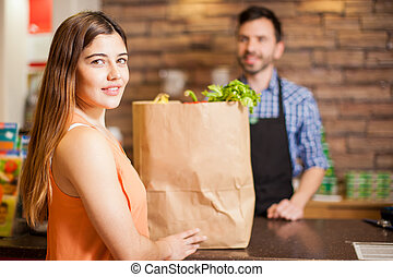 Pretty brunette buying some groceries