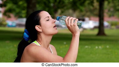 Pretty brunette drinking from water