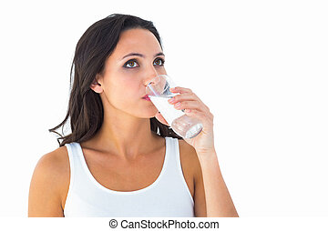 Pretty brunette drinking glass of water on white background