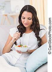 Pretty brunette eating salad on couch