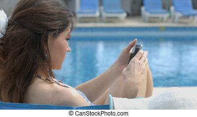 Pretty brunette female browsing internet on smartphone near pool