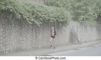 Pretty brunette fitness woman running outdoors