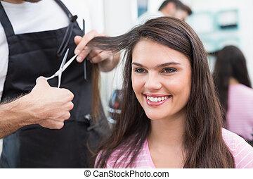 Pretty brunette getting her hair cut at the hair salon