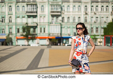 Pretty brunette girl wearing trendy dress and glasses, posing at the street. Space for text