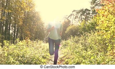 Pretty brunette girl with ponytail running in autumn forest. Sunny day, blazing sun. Super slow motion steadicam shot