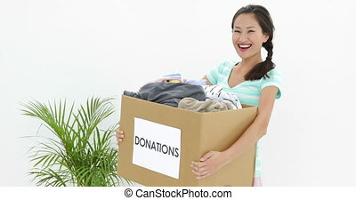 Pretty brunette holding donation box full of clothes smiling...