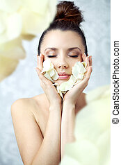 Pretty brunette holding petals close to face