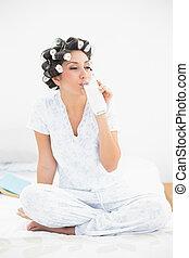 Pretty brunette in hair rollers drinking glass of milk