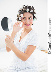 Pretty brunette in hair rollers looking in hand mirror and ...