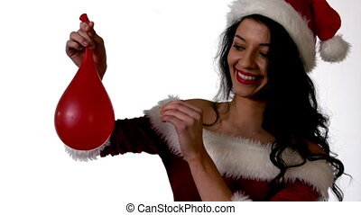 Pretty brunette in santa outfit popping a water balloon in slow motion