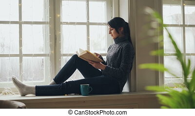 Pretty brunette in sweater and jeans is reading book sitting...