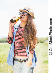 Pretty brunette in the park drinking beer