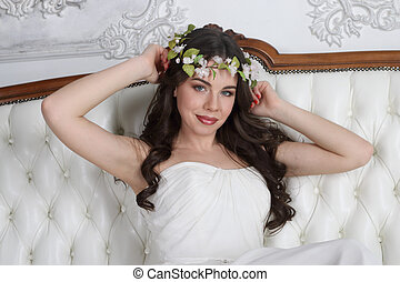 Pretty brunette in wreath and in white dress poses on couch in studio
