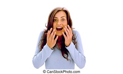Pretty brunette is happily surprised on white background in...