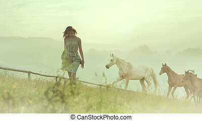 Pretty brunette lady resting among horses