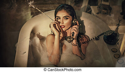 Pretty brunette lady taking a bath and smoking
